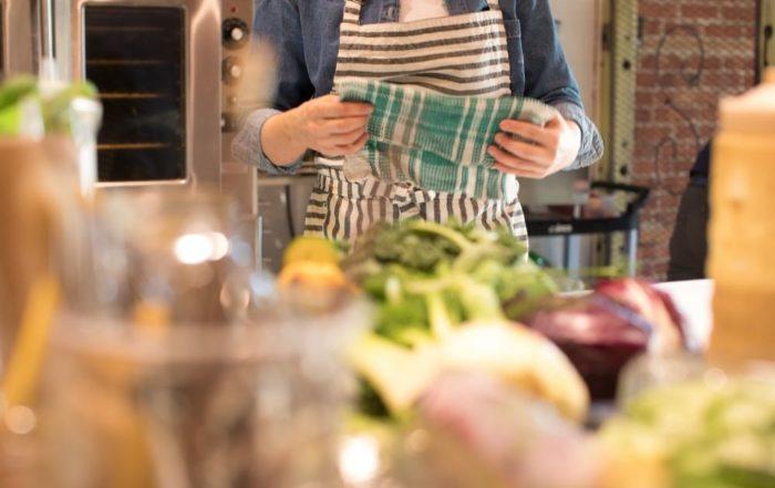 Im Vordergrund ist unscharf Gemüse und Kochzubehör zu erkennen. Im Hintergrund ist Fokussiert eine Person, die saisonale Gerichte kocht