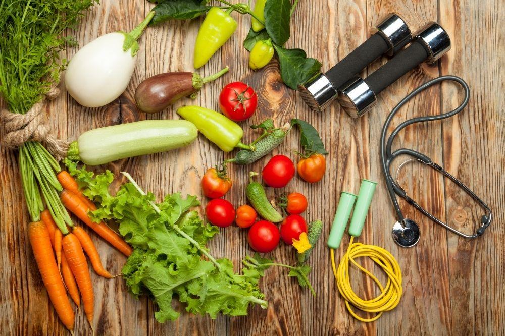 Obst, Gemüse, Hanteln und ein Stetoskop liegen auf einer Holzplatte