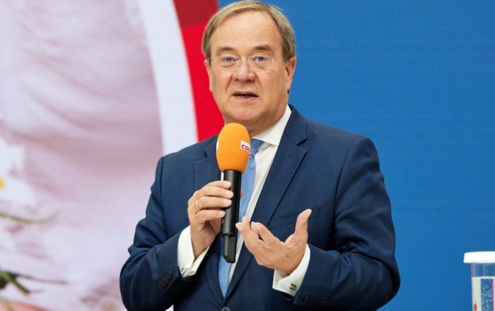 Auf dem Bild ist Kanzlerkanditat der CDU Armin Laschet zu sehen. In seiner Hand hält er ein Mikrofon in das er gerade spricht. Der Hintergrund des Bildes ist blau und