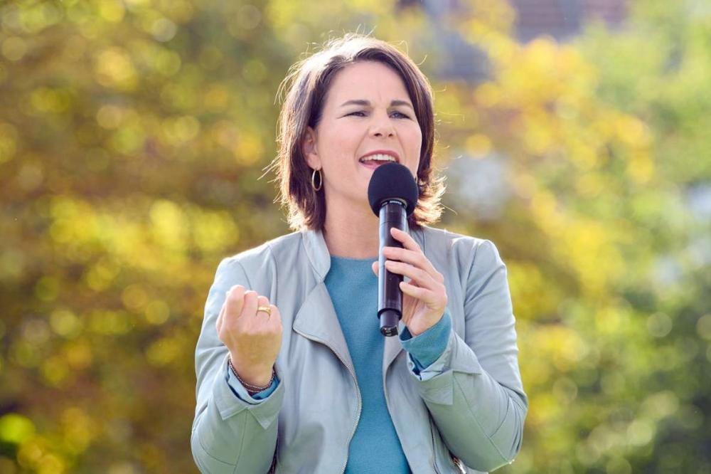 Auf dem Bild, die Kanzlerin der Grünen Annalena Baerbock, die ein Mikrofon in der Hand hält und draußen in der Natur eine Rede gibt