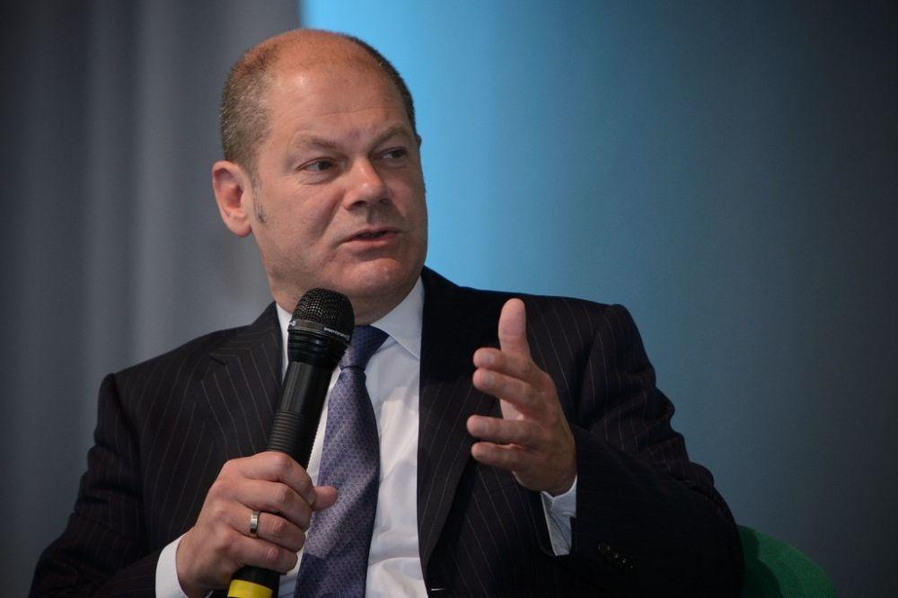Der Kanzlerkandidat der SPD Olaf Scholz redet mit einem Mikrophon in der Hand vor einem blauen Hintergrund.