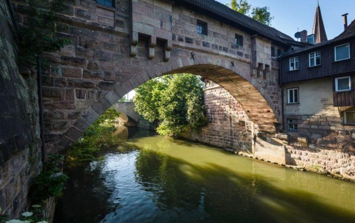 Ein Fluss fließt unter einer Brücke durch. Dieses Bild soll zum Naturschutz in Nürnberg bewegen.
